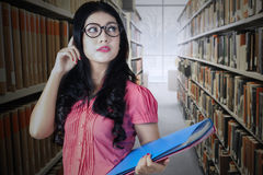 Estudiante hermoso con los vidrios en biblioteca Fotos de archivo libres de regalías