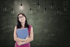 Estudiante hermoso debajo de bombillas en clase Imágenes de archivo libres de regalías