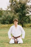 Estudiante hermoso del karate que se sienta en un fondo natural Concepto del este de la lección que lucha Copie el espacio Foto de archivo
