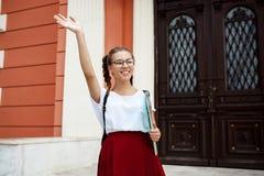 Estudiante hermoso en vidrios que sonríe, saludo, sosteniendo carpetas al aire libre Fotos de archivo