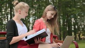 Estudiante hermoso joven dos con el ordenador portátil a disposición en un banco en parque verde estudio Discusión Vista lateral metrajes
