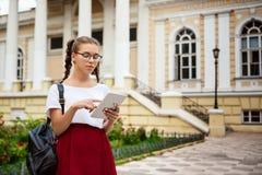 Estudiante hermoso joven en los vidrios que miran la tableta al aire libre, fondo del parque Fotos de archivo