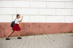 Estudiante hermoso joven en vidrios que camina abajo de la calle, sosteniendo carpetas Imagenes de archivo