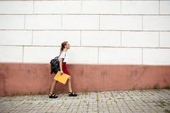 Estudiante hermoso joven en vidrios que camina abajo de la calle, sosteniendo carpetas Foto de archivo libre de regalías