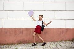 Estudiante hermoso joven en vidrios que camina abajo de la calle, sosteniendo carpetas Imágenes de archivo libres de regalías