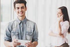 Estudiante hermoso joven Guy Uses Digital Tablet Imagenes de archivo