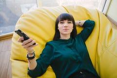 Estudiante hermoso joven que descansa entre el entrenamiento y la tenencia un teléfono Retrato en un cuarto con un bolso de la bu Imagen de archivo