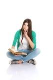 Estudiante hermoso joven que se sienta con el libro, lectura, aprendiendo. Foto de archivo libre de regalías