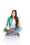 Estudiante hermoso joven que se sienta con el libro, lectura, aprendiendo. Fotografía de archivo libre de regalías