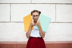 Estudiante hermoso joven trastornado en los vidrios que sostienen carpetas al aire libre Foto de archivo libre de regalías