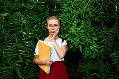 Estudiante hermoso joven trastornado en los vidrios que sostienen carpetas al aire libre, fondo del parque Fotografía de archivo libre de regalías