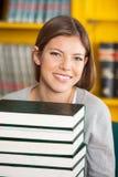 Estudiante hermoso With Piled Books que sonríe adentro Imágenes de archivo libres de regalías