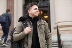 Estudiante hermoso que camina en campus de la universidad con una mochila a la clase foto de archivo libre de regalías