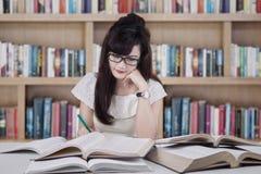 Estudiante hermoso que estudia en la biblioteca Fotos de archivo