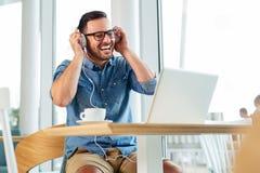 Estudiante hermoso que estudia en un café con sus auriculares encendido - Imagen imagenes de archivo
