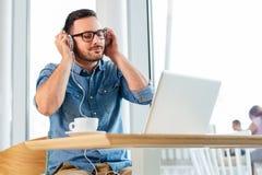 Estudiante hermoso que estudia en un café con sus auriculares encendido - Imagen foto de archivo