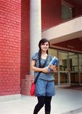 Estudiante hermoso que se coloca con los libros. Imagen de archivo libre de regalías