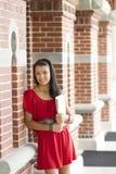 Estudiante hermoso que se inclina contra una pared de ladrillo Imagen de archivo