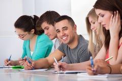 Estudiante hermoso que se sienta con los compañeros de clase que escriben en el escritorio Foto de archivo libre de regalías