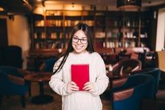 Estudiante hermoso que sostiene el libro en biblioteca Imagenes de archivo