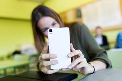 Estudiante hermoso que usa su teléfono móvil en una universidad Imagen de archivo