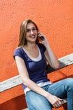 Estudiante hermoso sonriente que se sienta en un banco con smartphone Imágenes de archivo libres de regalías