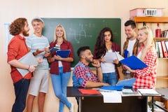 Estudiante High School Group que discute la sala de clase de la universidad, comunicación casual de la gente joven Fotos de archivo libres de regalías