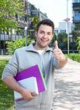 Estudiante hispánico feliz en el campus que muestra el pulgar para arriba Foto de archivo