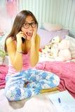 Estudiante hispánico feliz en el dormitorio que recibe sorpresa de las buenas noticias en el teléfono Imagen de archivo