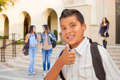 Estudiante hispánico masculino joven Boy Gives Thumbs para arriba en campus foto de archivo libre de regalías
