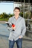 Estudiante Holding Book And Juice Bottle On Campus Imagen de archivo libre de regalías