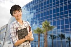 Estudiante Holding Books de la raza mixta delante del edificio Imagen de archivo libre de regalías