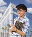 Estudiante Holding Books de la raza mixta delante del edificio Foto de archivo libre de regalías
