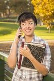 Estudiante Holding Books y el hablar de la raza mixta en el teléfono Fotografía de archivo