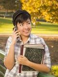 Estudiante Holding Books y el hablar de la raza mixta en el teléfono Imágenes de archivo libres de regalías
