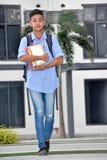 Estudiante impasible Walking On Campus del muchacho foto de archivo