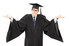 Estudiante incierto en vestido de la graduación que gesticula con las manos Imagen de archivo libre de regalías