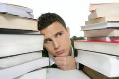 Estudiante infeliz joven con los libros empilados Foto de archivo