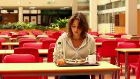 Estudiante infeliz que come el almuerzo solamente almacen de video