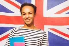 Estudiante inglés sonriente con los libros de texto Fotos de archivo libres de regalías