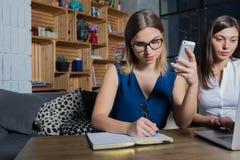 Estudiante internacional femenino que aprende usando el teléfono móvil fotos de archivo libres de regalías