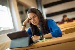 Estudiante joven aburrido en la sala de clase de la universidad Imagen de archivo