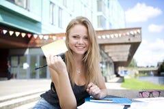 Estudiante joven afuera con los libros que muestran la nota pegajosa Imagenes de archivo