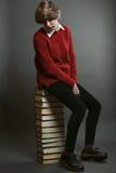 Estudiante joven asentado en una pila de libros Foto de archivo