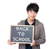 Estudiante joven asiático con la pizarra que muestra de nuevo a escuela Imagen de archivo libre de regalías