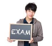 Estudiante joven asiático con la pizarra que muestra un examen de la palabra Foto de archivo