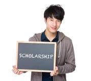 Estudiante joven asiático con la pizarra que muestra una beca de la palabra Foto de archivo libre de regalías
