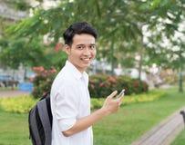 Estudiante joven asiático feliz que usa el teléfono móvil Imagenes de archivo