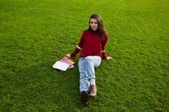 Estudiante joven atractivo que se relaja en verde enorme después de una conferencia larga en la universidad Imagenes de archivo