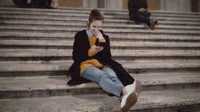Estudiante joven atractivo que se sienta en la escalera y que usa smartphone Muchacha que charla con tecnología de la pantalla tá almacen de metraje de vídeo